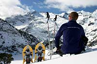 Exodus leader with snowshoes looking over the Aigues Tortes National Park in the Pyrenees