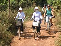 Exodus cyclist riding with Vietnamese girls, Mekong delta