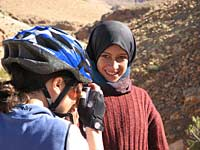 Biker taking photograph, local girl watching, Atlas Mountains