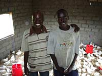 Kelvin with the chicken coop we helped him build - to create income for the community and employment for the young lad Danny he is with.