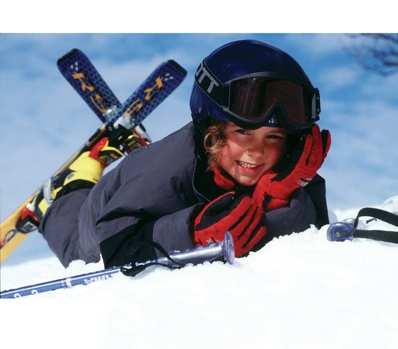 Young skier lying in the snow