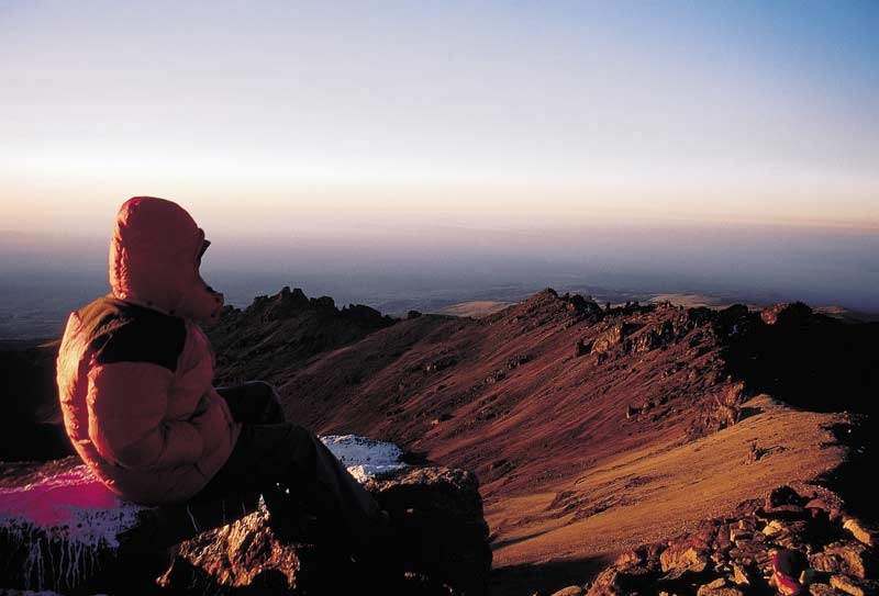 Trekker watching sunrise on Mt Kenya