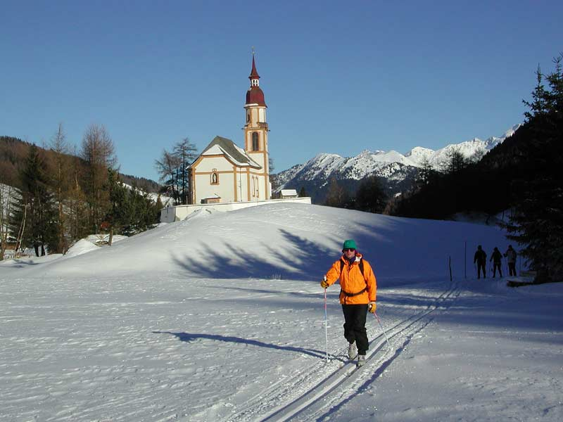 Cross-country skiing by church at Trins