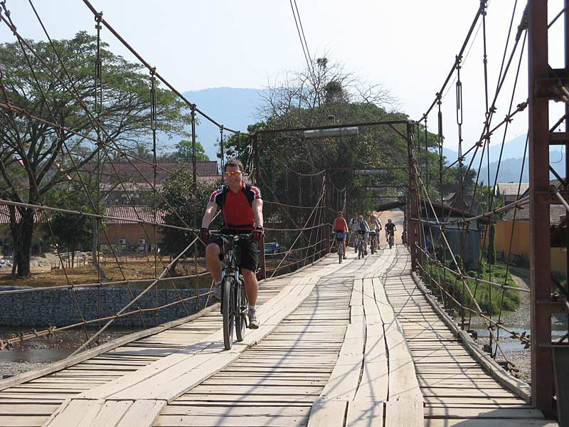 Cyclist crossing bridge, Vang Vieng