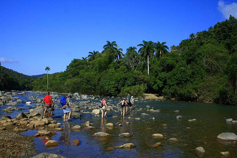 Walkers crossing a river, Cuba