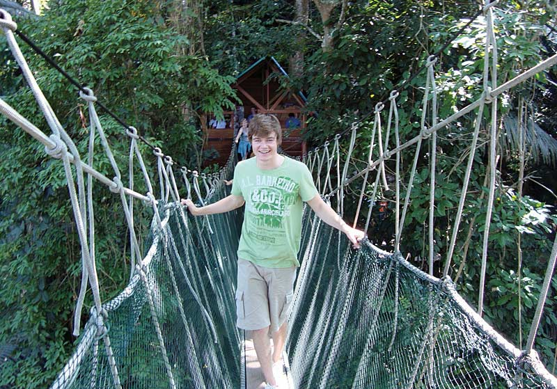 Teenager negotiating jungle canopy suspension bridges, Borneo
